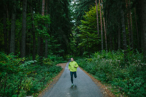 Man running and exercising for trail run on a path in an old green forest.