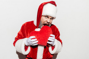 Man santa claus holding and biting red heart