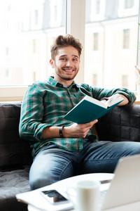 Man siiting on sofa reading book near the table and looking at camera in office. Coworking