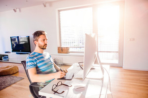Man sitting at the desk working from home on computer, using a graphic tablet