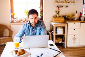 Man sitting at the kitchen table working from home on laptop