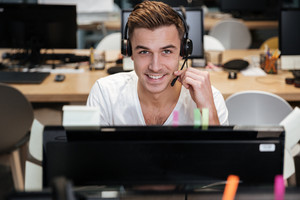 Man sitting by the computer in headphone and looking at camera. Coworking