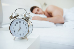 Man sleeping on bed. Focus on clock which on nightstand near the bed.