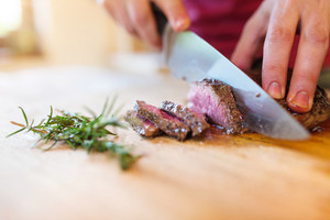 Man slicing a grilled beef stead on a wooden cutting board