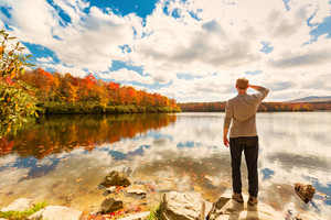 Man standing at he edge of a lake in autumn