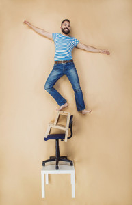 Man standing dangerously on a pile of chairs. Studio shot on a beige background.