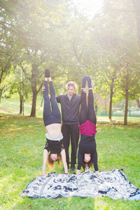 Man teaching two young girls how to handstand outdoor in a park in autumn back light - teaching, training, healthy concept