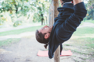 Man training outdoor in a park using rings - gymnastic, training, sportive concept