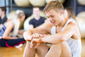 Man Using Smart Watch While Friends Sitting In Gym