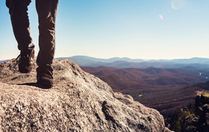 Man walking on the edge of a cliff high above the mountains below