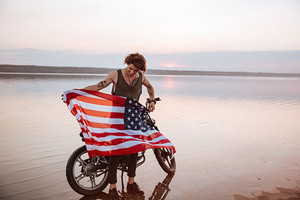 Man waving american flag at the desert standing near motorcycle