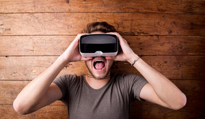 Man wearing virtual reality goggles. Facial expression, screaming. Flat lay. Studio shot, wooden background