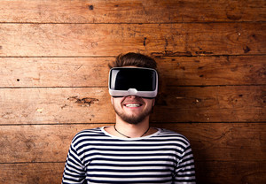 Man wearing virtual reality goggles. Flat lay. Studio shot, wooden background