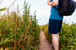 Man with a backpack walking down a nature trail