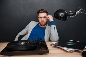 Man with gramophone sitting on the table in studio. looking at the camera. isolated black background