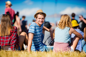 Man with hat, group of teenagers at summer music festival, sitting on the grass, back view, rear, viewpoint
