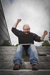 Man with his laptop celebrate an achievement or a winning. Sitting in stairs outside.