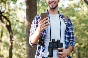 Man with phone in forest. man in shirt with binoculars and backpack. cropped image