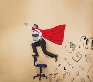 Manager wearing cloak of superman. Studio shot on a beige background.