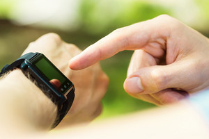 Mans hand pointing at his smartwatch outside