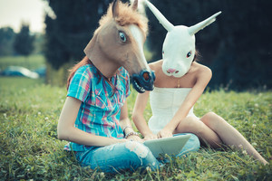 mask horse and rabbit women sisters friends using smartphone and tablet in the park