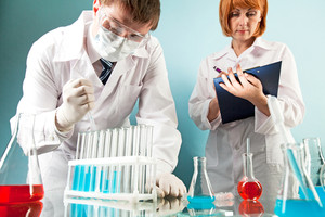 Masked clinician working with flasks in laboratory with nurse making notes near by
