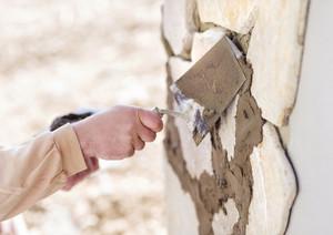 Mason putting decorative natural stones on a wall
