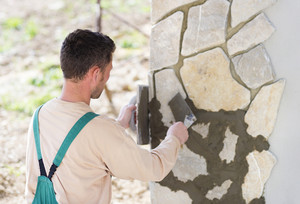 Mason putting decorative natural stones on a wall