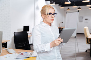 Mature attractive businesswoman standing in office with pc tablet