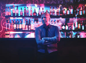 Mature bald man standing by bar counter in night clubv