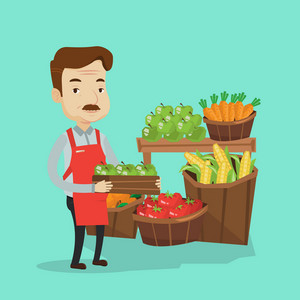 Mature male supermarket worker holding a box full of apples. Friendly worker of grocery store standing in front of section with vegetables and fruits. Vector flat design illustration. Square layout.
