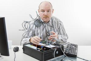 Mature Technician Repairing Computer At Desk