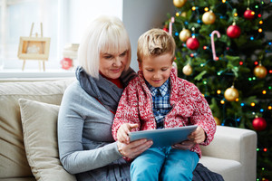 Mature woman and her grandson networking by Chrismas tree