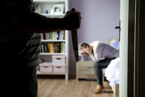 Mature woman siiting on the bed is scared of man with knife. Woman is victim of domestic violence and abuse.