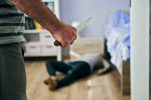 Mature woman sitting on the floor is scared of man with knife. Woman is victim of domestic violence and abuse.
