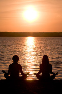 Meditating couple sitting in pose of lotus during wonderful sunset