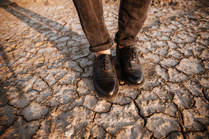 Men legs standing at the dessert dry ground