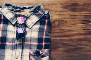 Men's plaid shirt and colored glasses on a wooden background. Top view, copy space.