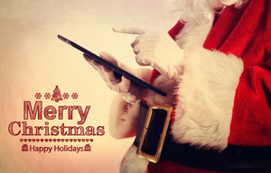 Merry Christmas message with Santa Claus with tablet