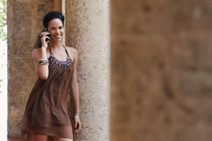 mid adult hispanic woman talking on mobile phone and leaning on columns outdoors. Horizontal shape, front view, copy space