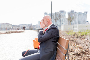 Middle age businessman sitting on a bench outdoor tired - stress, tension, business concept