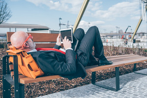 Middle age caucasian businessman relaxing lying down on a bench using tablet - relax, business, resting concept