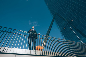 Middle-age contemporary businessman leaning on a handrail holding smart phone - work, business, conversation concept
