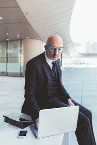 Middle-age contemporary businessman outdoor in the city multitasking using devices - stock market, trading, finance concept