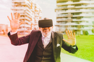 Middle-age contemporary businessman outdoor in the city using 3d viewer - videogame, augmented reality, 3d viewer concept