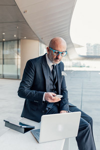 Middle-age contemporary businessman outdoor in the city, using smart phone hand hold and computer - business, multitasking, work concept