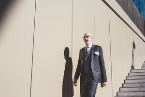 Middle-age contemporary businessman outdoor in the city walking downstairs serious