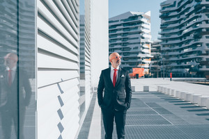 Middle-age contemporary businessman posing outdoor in the city, hand in pocket, overlooking - pensive, serious, thoughtful concept
