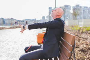 Middle-age contemporary businessman sitting outdoor on a bench in a city park stretching - business, stretching, relaxing concept