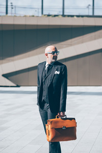 Middle-age contemporary businessman walking outdoor in the city, holding a briefcase - business, career, manager concept